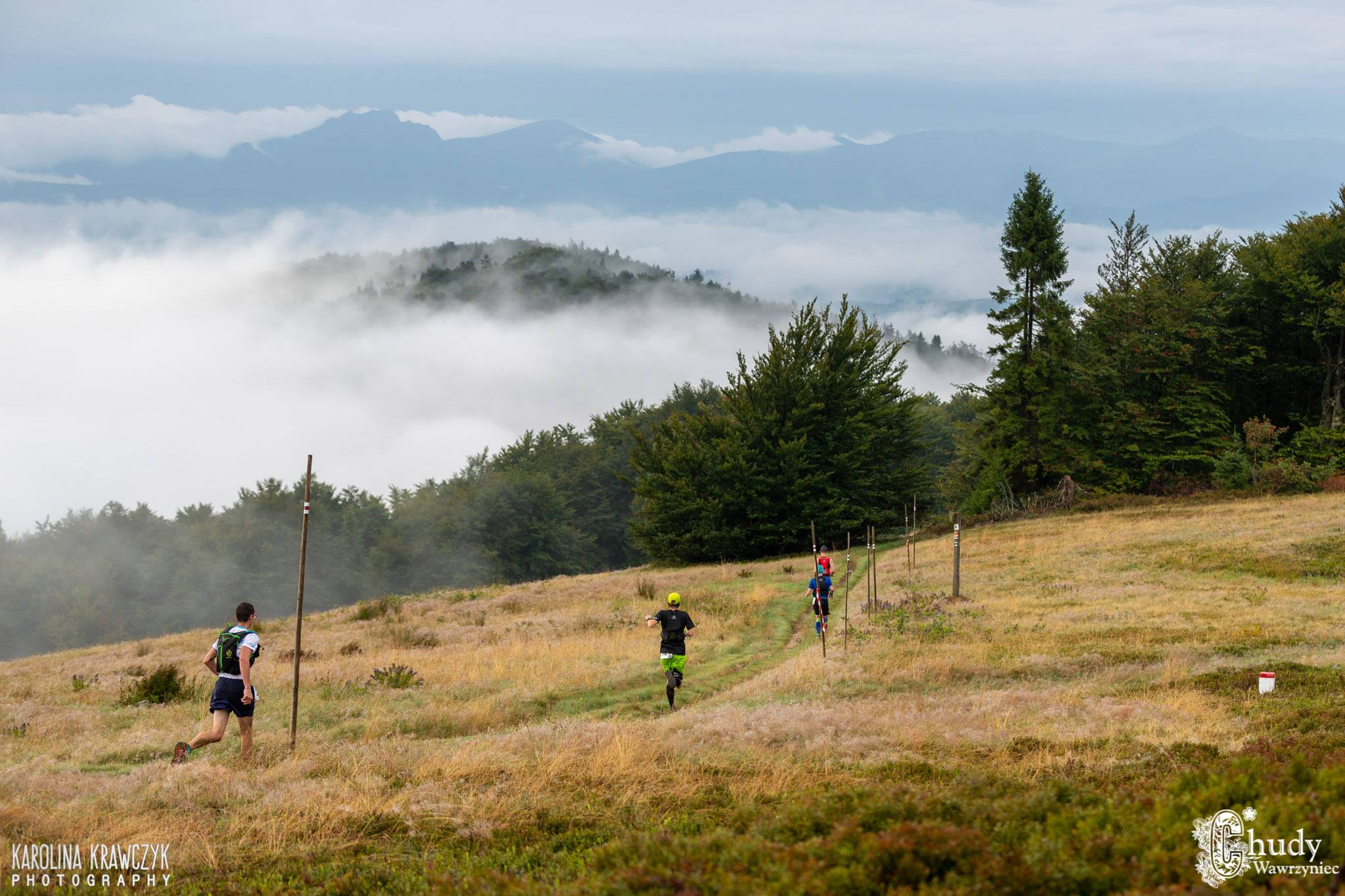 Górska polana, góry i chmury w tle, biegacze na polanie