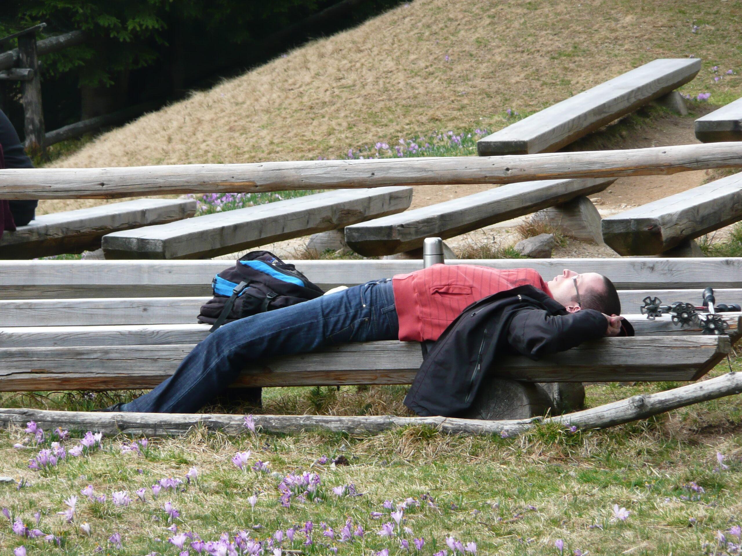 Turysta leży na ławce, odpoczywa