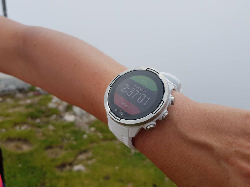 ręka z zegarkiem na górskim tle