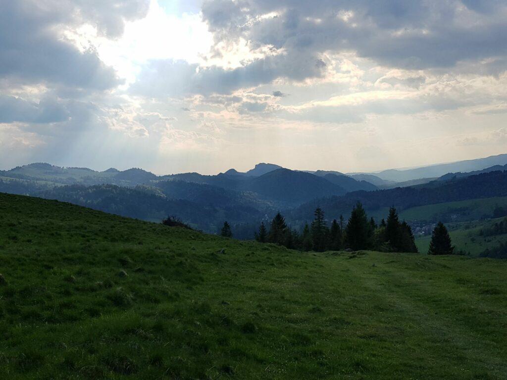 Widok na góry, niebo, chmury, słońce przebija się.