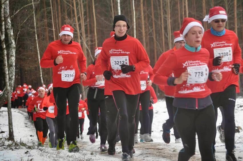 biegacze na czerwono w lesie zimą na drodze