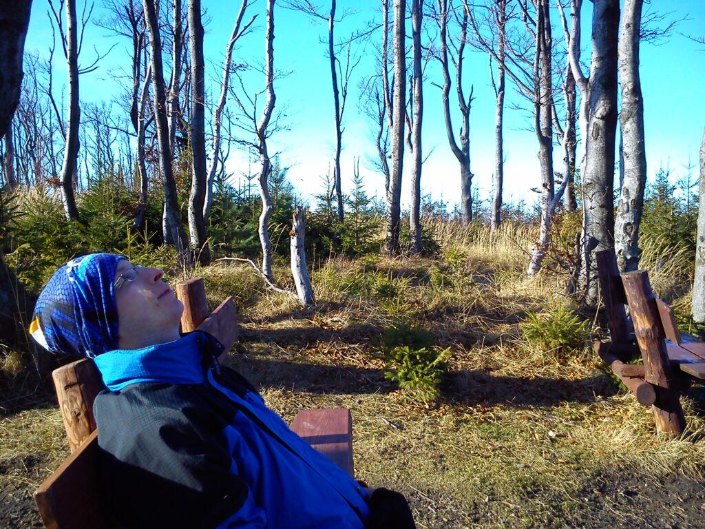 Mężczyzna widziany z profilu odpoczywa oparty na ławce w lesie