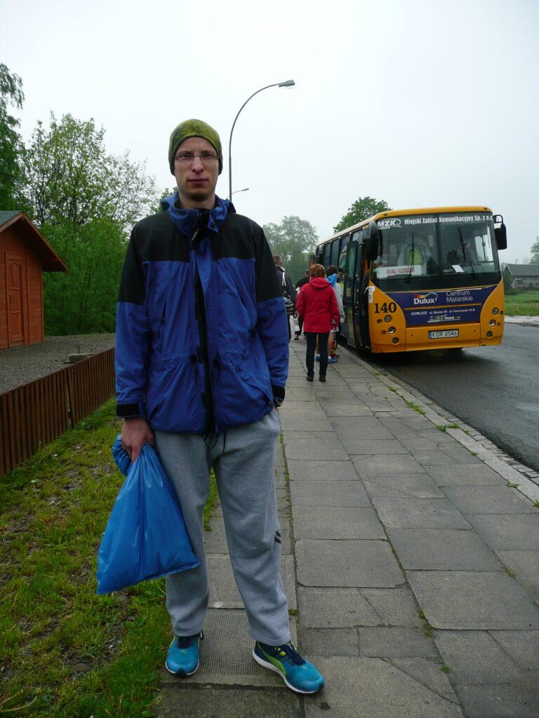 Mężczyzna na chodniku, w tle autobus.