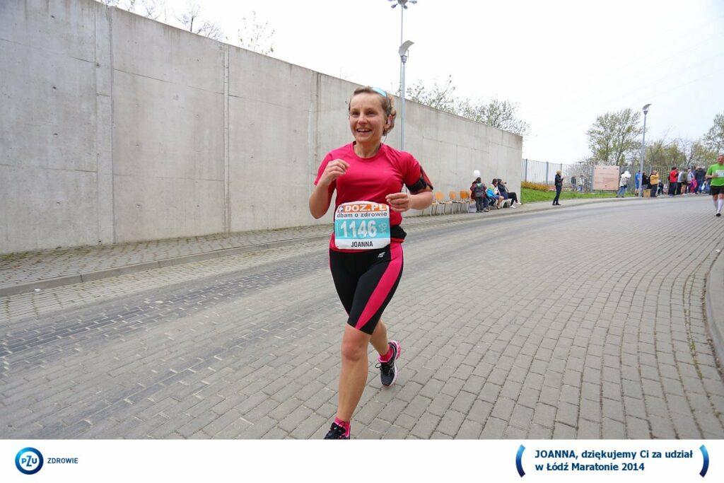 uśmiechnięta biegaczka zbiega ulicą w dół