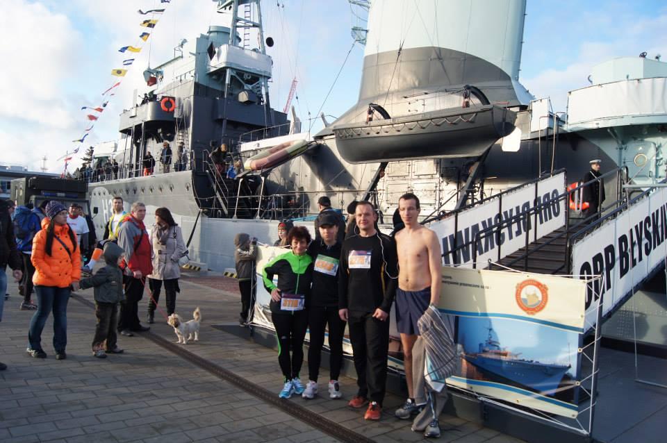 czworo biegaczy pozuje do zdjęcia przed okrętem wojennym, jeden mężczyzna z gołą klatką